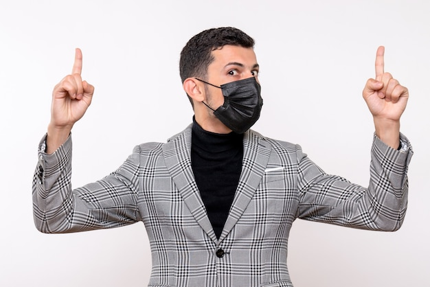 Vooraanzicht jonge man met zwart masker wijzend met vinger omhoog staande op witte geïsoleerde achtergrond