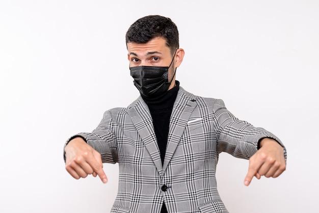 Vooraanzicht jonge man met zwart masker wijzend op vloer staande op witte geïsoleerde achtergrond