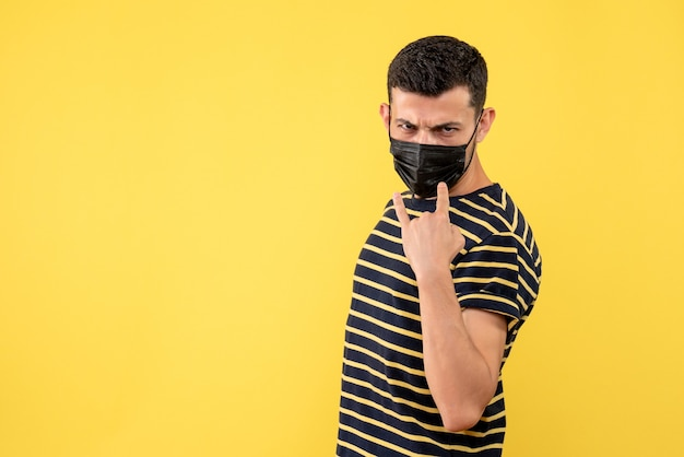 Vooraanzicht jonge man met zwart-wit gestreept t-shirt rock teken gele achtergrond vrije ruimte maken
