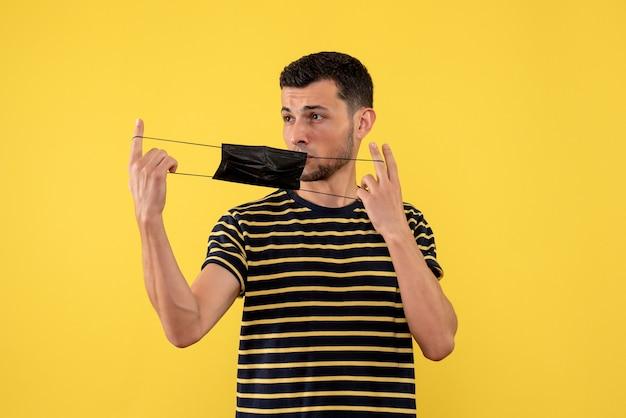 Vooraanzicht jonge man met zwart-wit gestreepte t-shirt met zwarte masker gele achtergrond