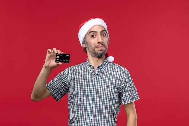 Vooraanzicht jonge man met zwarte bankkaart op de rode achtergrond