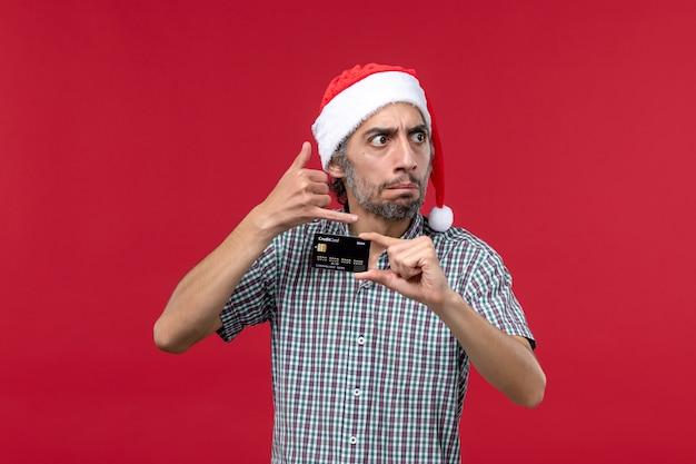 Vooraanzicht jonge man met zwarte bankkaart op lichtrode achtergrond