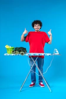 Vooraanzicht jonge man meten hemd op zichzelf op blauwe achtergrond schone wasmachine huis kleur mens