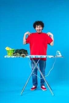 Vooraanzicht jonge man meten hemd op zichzelf op blauwe achtergrond schone wasmachine huishoudelijk werk huis kleur mens
