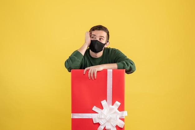 Vooraanzicht jonge man na te denken over iets achter grote geschenkdoos op geel