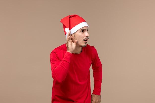 Vooraanzicht jonge man nauw luisteren op bruine achtergrond emotie kerstvakantie