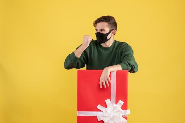 Vooraanzicht jonge man op zoek naar iets met woede achter grote geschenkdoos op geel