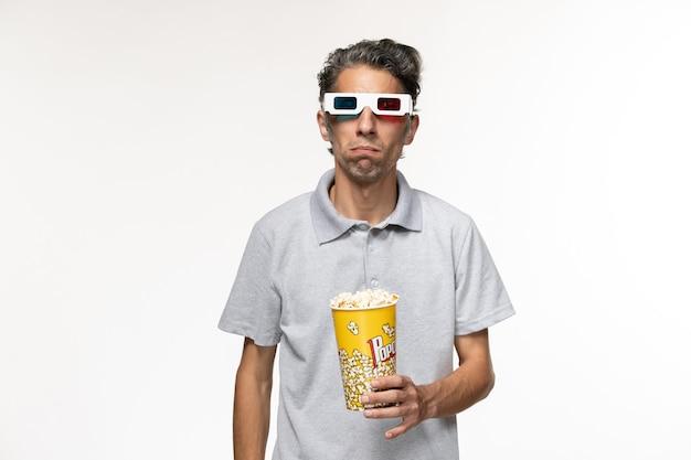 Vooraanzicht jonge man popcorn eten in d zonnebril op licht wit oppervlak