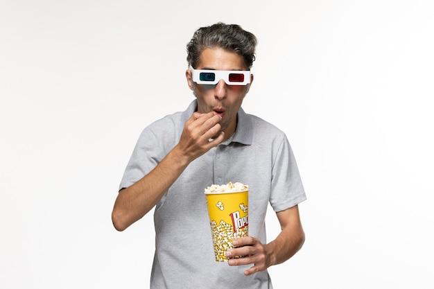 Vooraanzicht jonge man popcorn eten in d zonnebril op witte ondergrond