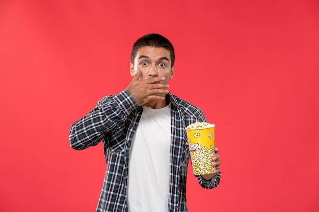 Vooraanzicht jonge man popcorn pakket houden en kijken naar film op de lichtrode muur mannelijke bioscoop bioscoop film leuke tijden