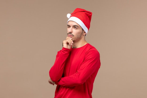 Vooraanzicht jonge man poseren met denken gezicht op bruine achtergrond emotie vakantie man