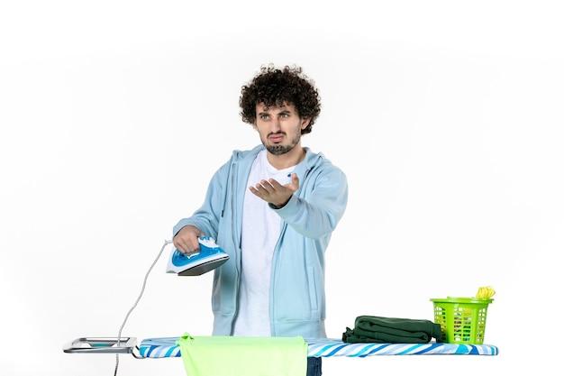 Vooraanzicht jonge man probeert ijzer te repareren op witte achtergrond ijzer kleur man wasserij kleding huishoudelijk werk schoonmaken emotie