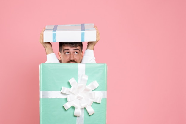 Vooraanzicht jonge man probeert te verbergen in huidige doos op de roze kerstkleur emotie slaap pyjama gezelschapsspel