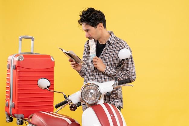 Vooraanzicht jonge man rond fiets met vliegticket op gele achtergrond road trip vakantie rit reis