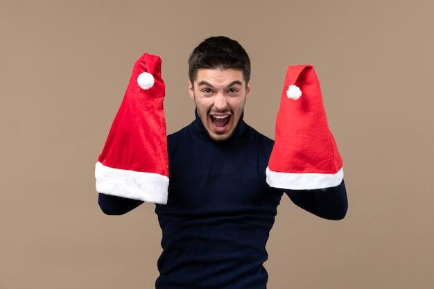 Vooraanzicht jonge man spelen met rode kappen op bruin bureau kerstmis emotie nieuwjaar