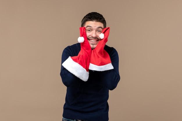 Vooraanzicht jonge man spelen met rode kappen op bruin bureau kerstvakantie emotie