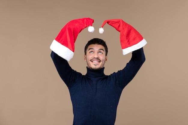 Vooraanzicht jonge man spelen met rode kappen op bruine achtergrond emotie kerstvakantie