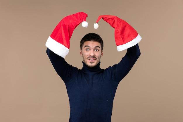 Vooraanzicht jonge man spelen met rode kappen op bruine achtergrond emoties kerstvakantie