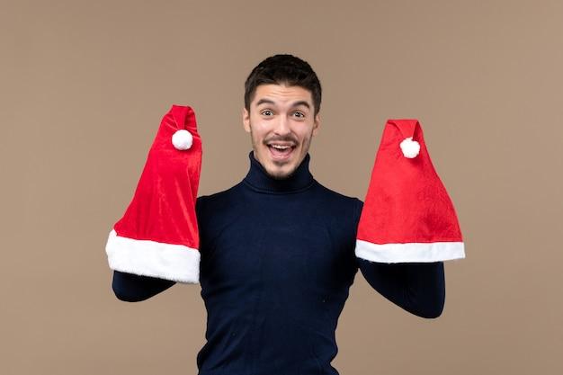 Vooraanzicht jonge man spelen met rode kappen op bruine achtergrond kerstmis emoties nieuwjaar