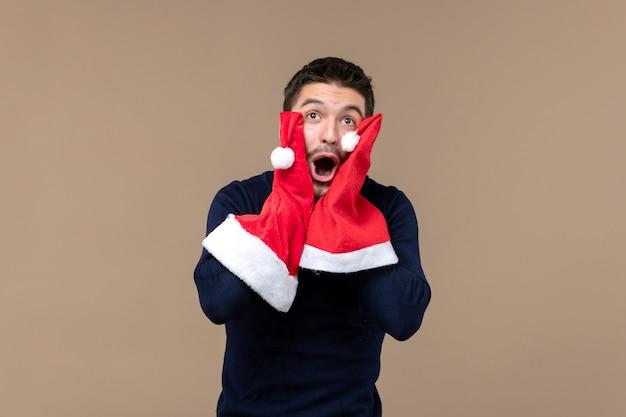 Vooraanzicht jonge man spelen met rode kappen op bruine achtergrond kerstvakantie emoties