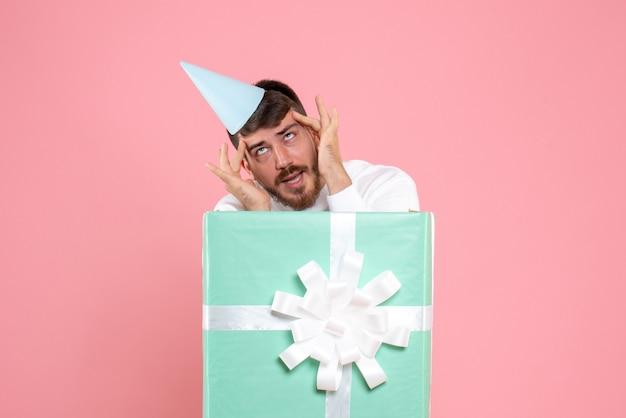 Vooraanzicht jonge man staande in huidige doos op de roze kleur emotie xmas nieuwjaar foto mens