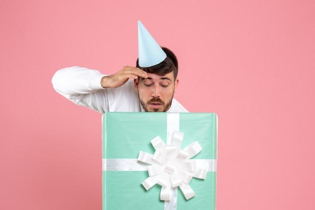Vooraanzicht jonge man staande in huidige doos op lichtroze foto kleur menselijke emotie xmas pyjama party
