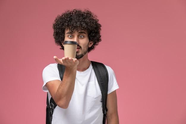 Vooraanzicht jonge man starend naar zijn papieren koffiekopje