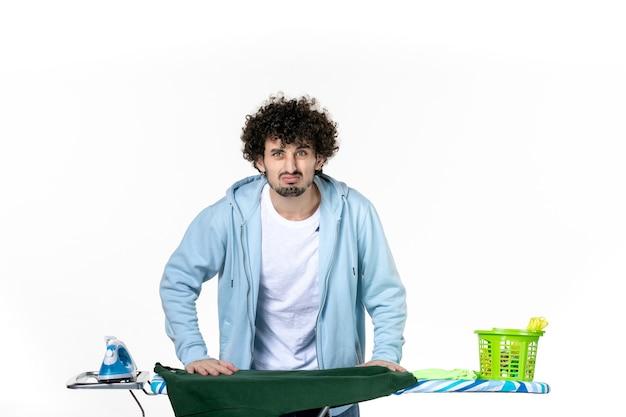 Vooraanzicht jonge man strijken achter bord op witte achtergrond huishoudelijk werk strijken wasgoed emotie kleuren menselijk