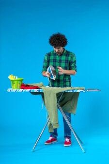 Vooraanzicht jonge man strijken groene trui aan boord op blauwe achtergrond mens schoon wassen huishoudelijk werk kleur huis
