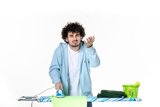 Vooraanzicht jonge man strijken handdoek aan boord op witte achtergrond ijzer kleur man huishoudelijk werk was foto kleding