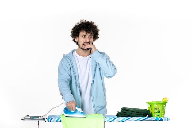 Vooraanzicht jonge man strijken handdoek aan boord op witte achtergrond ijzer kleur man schoonmaak foto kleding huishoudelijk werk