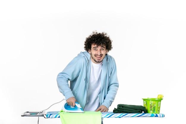 Vooraanzicht jonge man strijken handdoek op witte achtergrond ijzer kleur man schoonmaak huishoudelijk werk foto's kleding