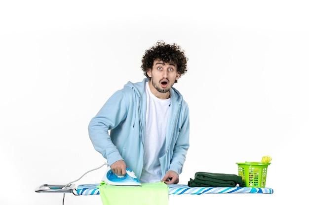 Vooraanzicht jonge man strijken handdoek op witte achtergrond ijzer kleur man schoonmaak huishoudelijk werk was foto kleding