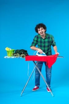 Vooraanzicht jonge man strijken rode kleren aan boord op blauwe achtergrond kleur huis wassen huishoudelijk werk menselijk schoon