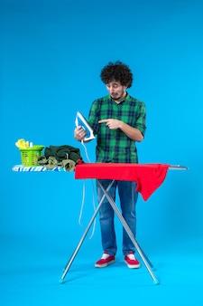 Vooraanzicht jonge man strijken rode kleren aan boord op blauwe achtergrond kleur wasmachine menselijk schoon huis