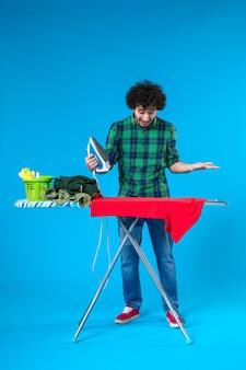 Vooraanzicht jonge man strijken rode kleren aan boord op blauwe achtergrond kleuren wasmachine huishoudelijk werk mens schoon huis