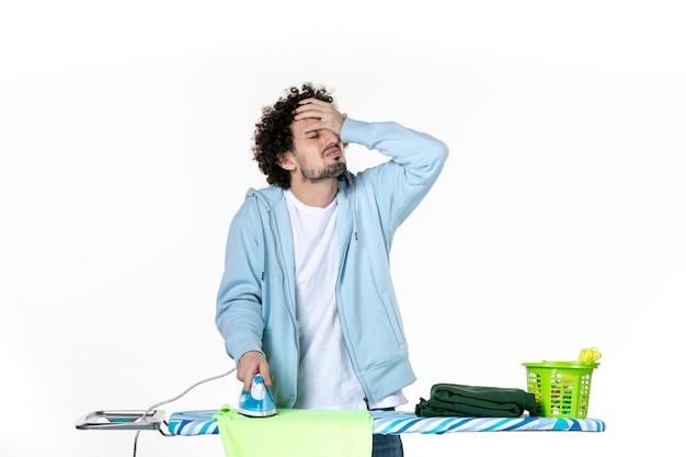 Vooraanzicht jonge man strijkende handdoek aan boord met teleurgesteld gezicht op witte achtergrond ijzer kleur man schoonmaak huishoudelijk werk foto kleding