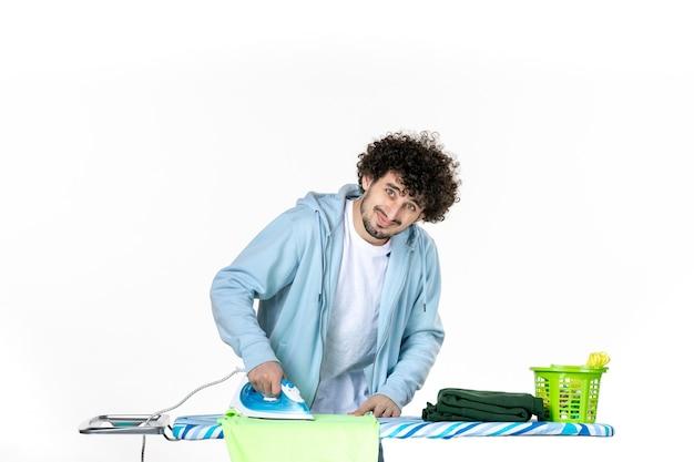 Vooraanzicht, jonge man, strijkende handdoek, op wit, achtergrond, ijzer, kleur, man, schoonmaken, huishoudelijk werk, wasserij, kleren