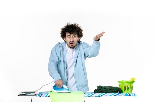 Vooraanzicht, jonge man, strijkende handdoek, op wit, achtergrond, ijzer, kleur, man, schoonmaken, wasserij, foto, clothes