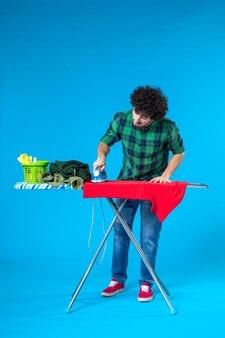 Vooraanzicht jonge man strijkt rood overhemd aan boord op blauwe achtergrond schone wasmachine huishoudelijk werk huis kleur mens