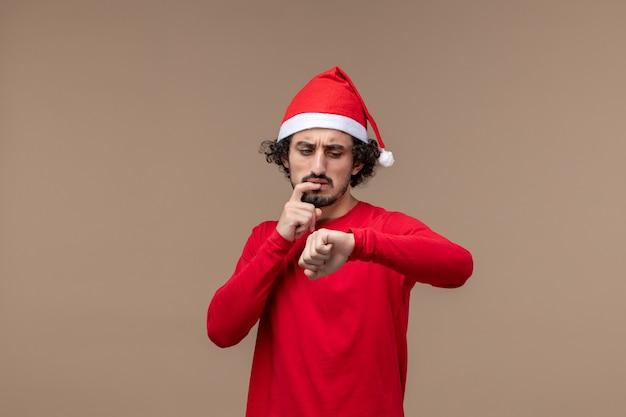 Vooraanzicht jonge man tijd op bruine bureau vakantie kerst emotie controleren