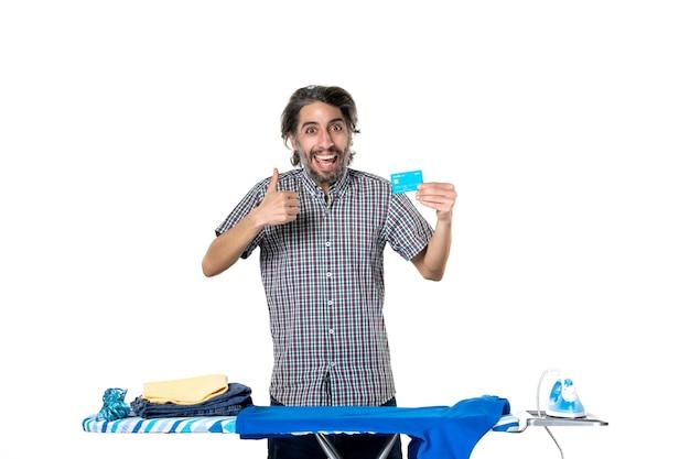 Vooraanzicht, jonge man, vasthouden, bankkaart, achter, strijkplank, op wit, achtergrond, ijzer, machine, thuis, geld, huishoudelijk werk, kleren, droog, wasserij