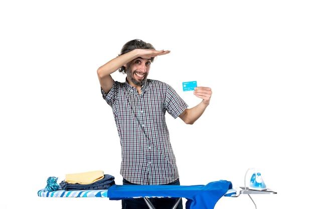 Vooraanzicht, jonge man, vasthouden, bankkaart, achter, strijkplank, op wit, achtergrond, ijzer, machine, thuis, geld, huishoudelijk werk, man, kleren, wasserij