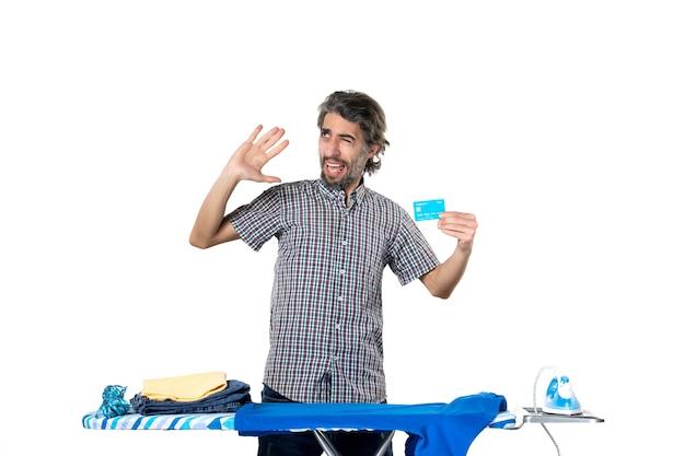 Vooraanzicht, jonge man, vasthouden, bankkaart, achter, strijkplank, op wit, achtergrond, ijzer, machine, thuis, huishoudelijk werk, man, kleren, geld, wasserette