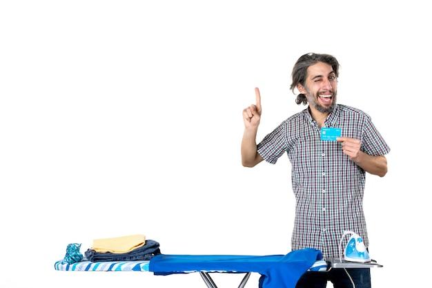 Vooraanzicht, jonge man, vasthouden, bankkaart, achter, strijkplank, op wit, achtergrond, ijzer, machine, thuis, man, kleren, geld, wasserette