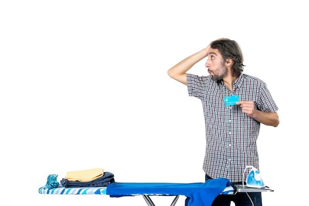Vooraanzicht, jonge man, vasthouden, bankkaart, achter, strijkplank, op wit, achtergrond, ijzer, wasserij, huishoudelijk werk, geld machine, home