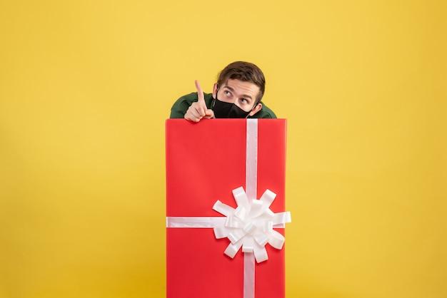 Vooraanzicht jonge man verstopt achter grote geschenkdoos op geel