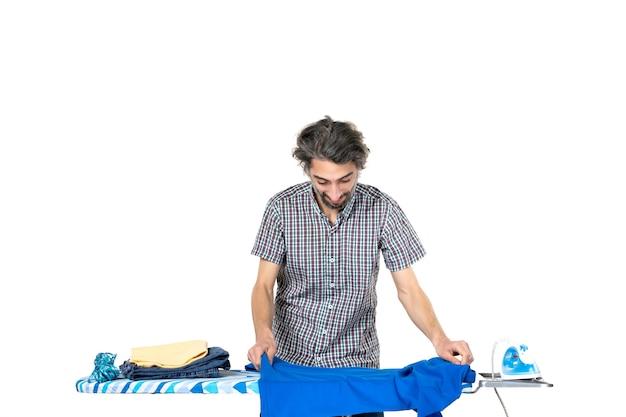 Vooraanzicht, jonge man, vouwen, blauw hemd, op, strijkplank, op wit, achtergrond, thuis, man, kleur, schoon, machine, kleren, ijzer, huishoudelijk werk