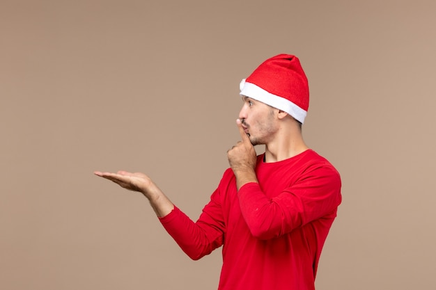Vooraanzicht jonge man vraagt om stilte te houden op bruin bureau kerst emotie vakantie