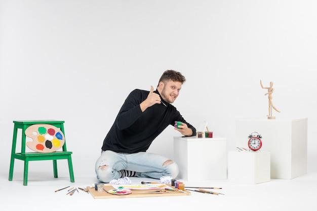 Vooraanzicht jonge man werken met verf in kleine blikjes op witte muur kunstenaar verf kunst kleur schilderijen foto tekenen foto